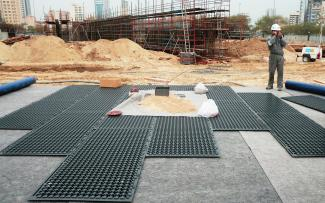 Worker laying out Stabilodrain® mats on the building site