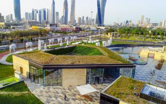 Building with a green roof amidst a green park in the city
