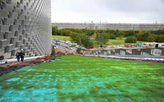 Ski slope on synthetic mats and grass growing through on a pitched roof